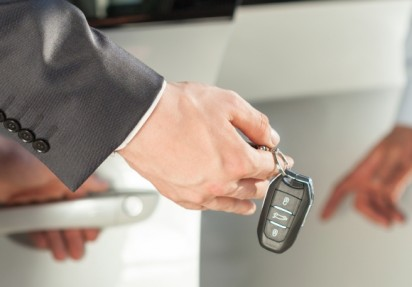 Close-up of man in suit with car keys in hand